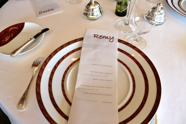 a folded menu on top of a plate on a restaurant table setting