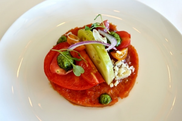 A plate of fresh vegetables including heirloom tomatoes with dollops of pesto