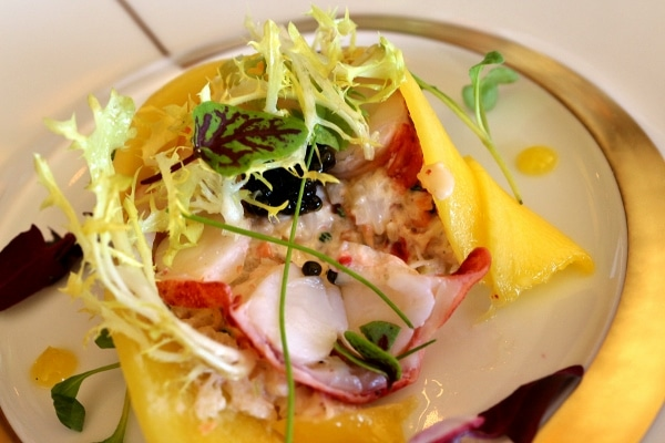 a half eaten plate of seafood salad wrapped with slices of mango