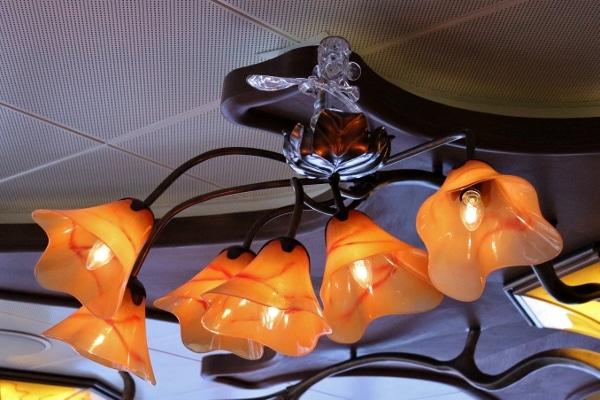 a glass Ratatouille figurine on top of an orange lighting fixture