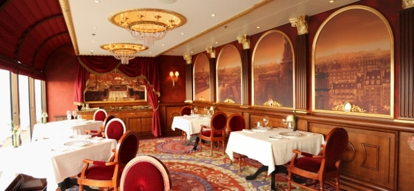 a very posh looking dining room with an ornate carpet and wall painting of Paris