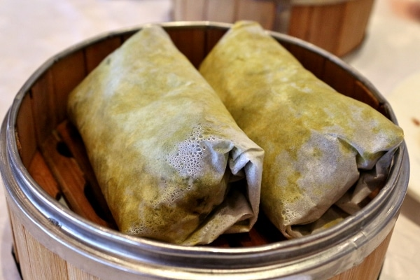 two leaf-wrapped packages in a bamboo steamer basket