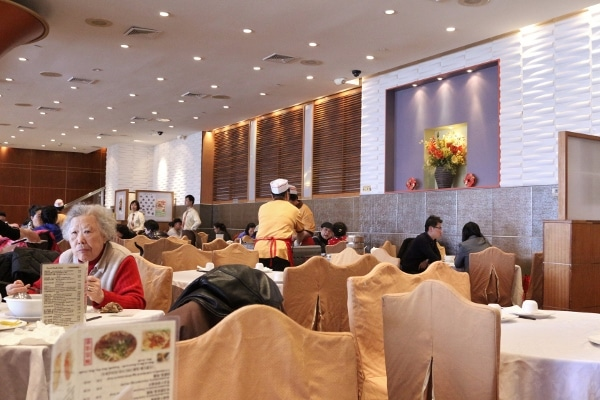 a large restaurant dining room with people pushing dim sum carts between tables