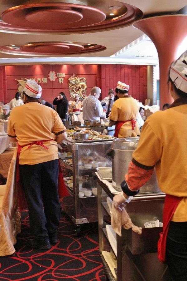 A group of woman pushing dim sum carts through a restaurant