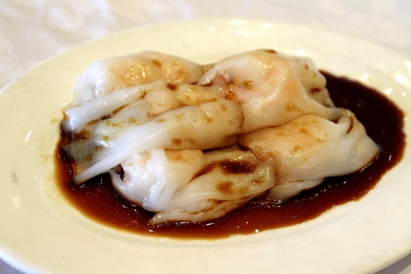 rice noodle rolls on a plate topped with soy sauce