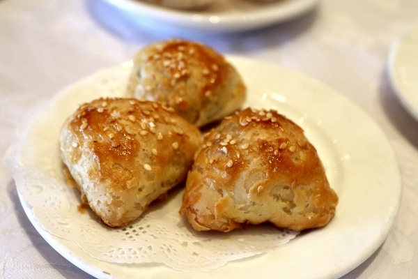 A closeup of a plate of sesame-topped flaky pastries