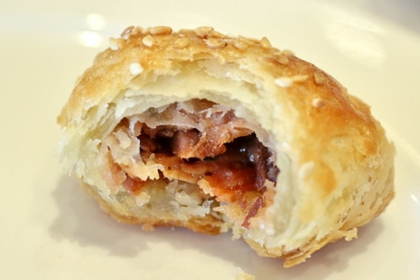 a half-eaten flaky pastry filled with barbecue pork