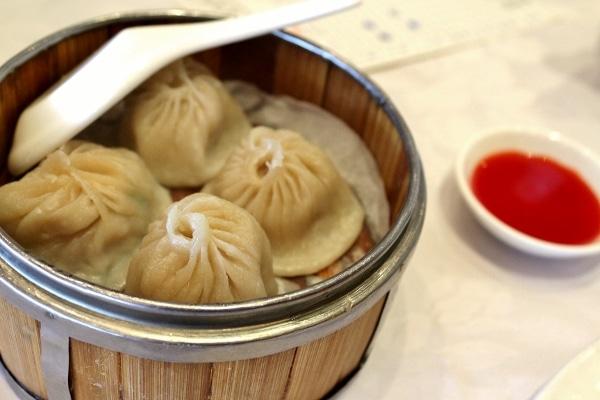 Shanghai soup dumplings in a bamboo steamer basket