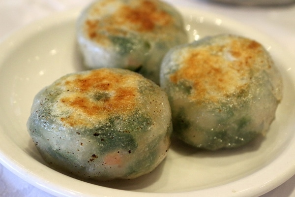 A plate of pan-fried dumplings with green filling showing through the wrapper