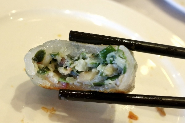 A close up of a half-eaten dumpling with green herb filling