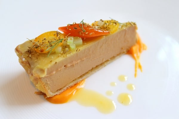 a closeup of a slice of foie gras tart topped with candied orange