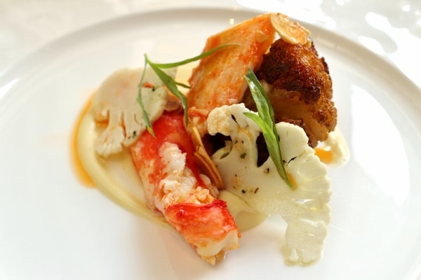 side view of an artful plate of food featuring crab meat and cauliflower