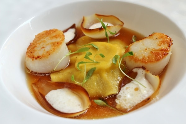 a big ravioli in brown broth served with seared scallops and charred onions
