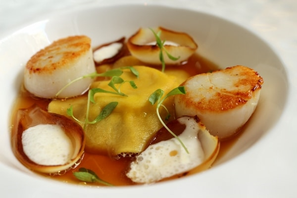side view of a big ravioli in broth served with seared scallops and charred onions