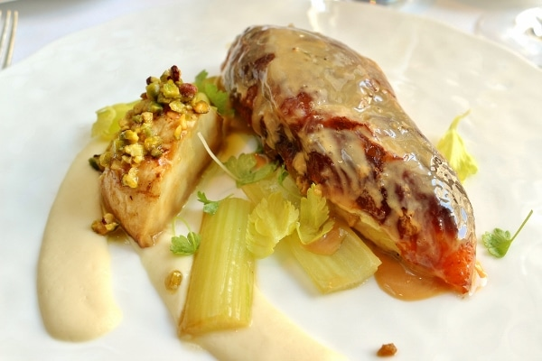 a glazed chicken breast served with pistachios and celery