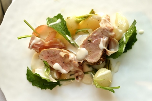 an artful plate of pork with onions, greens, and a delicate white sauce
