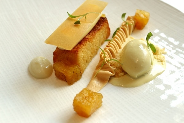 a rectangular piece of cake served with custard and ice cream