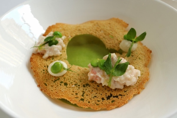 closeup of pea soup with a crispy cracker topping and dollops of shrimp custard