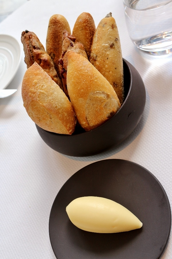 a modern looking bowl with small loaves of bread and a side of butter