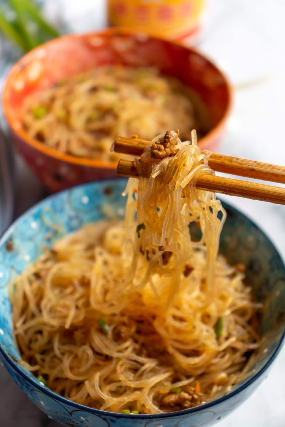 Wooden chopsticks lifting up bean thread noodles with ground pork from a floral blue bowl.