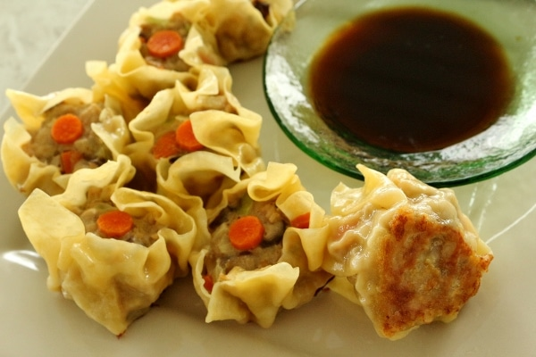 pan-fried siu mai dumplings garnished with carrot slices with a side of dipping sauce