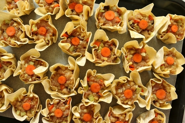 uncooked siu mai dumplings garnished with carrot slices on a tray