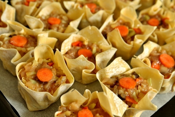 side view of uncooked siu mai dumplings arranged on a tray