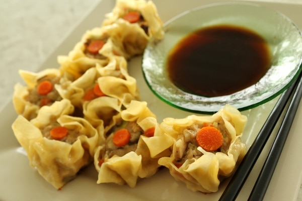 siu mai dumplings served in a square plate with a side of soy dipping sauce