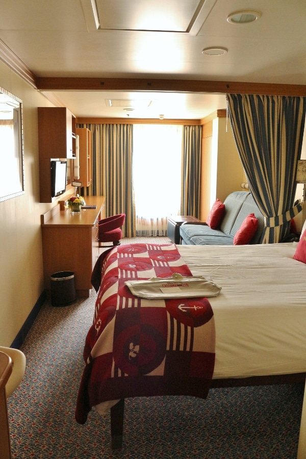 A cruise ship stateroom with a bed and couch