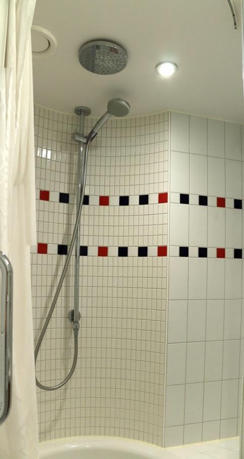 A tiled shower in a cruise ship bathroom