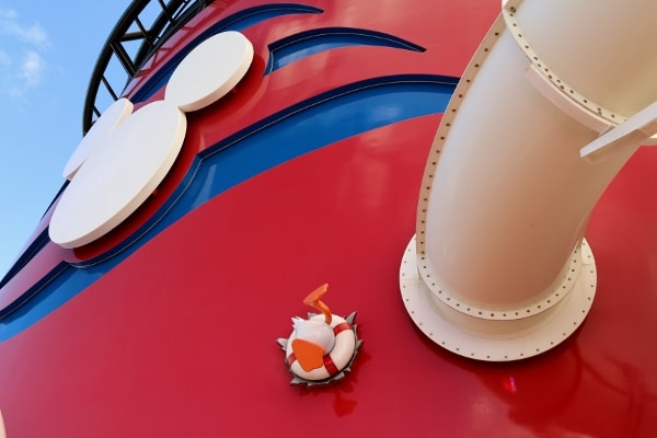 a large red cruise ship funnel with a white Mickey Mouse face on one side