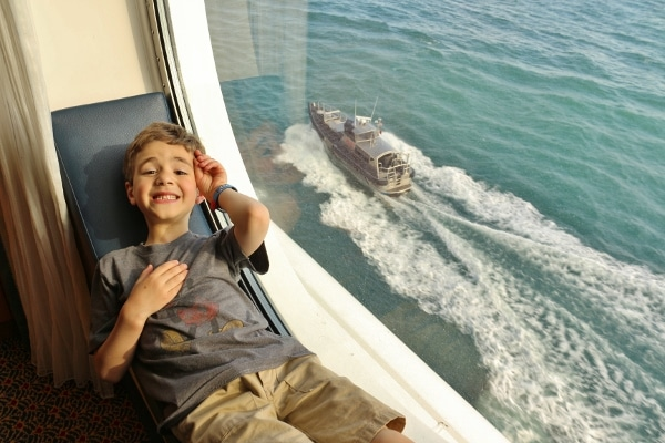 a boy laying in a porthole window with a pilot boat driving by outside