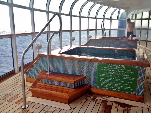 two tiled hot tubs with views of the ocean out floor-to-ceiling windows