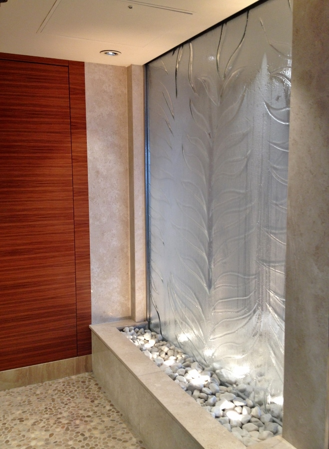 a glass waterfall area inside a spa relaxation room