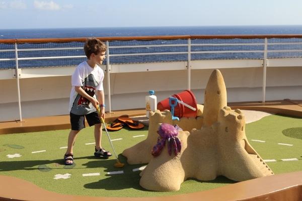 a boy playing mini golf on a cruise ship