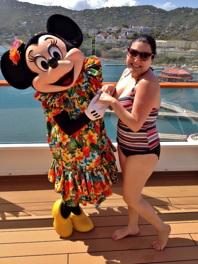 A woman posing with Minnie Mouse dressed in a tropical outfit
