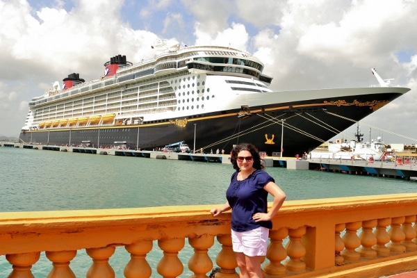 A person posing in front of a Disney Cruise Line ship