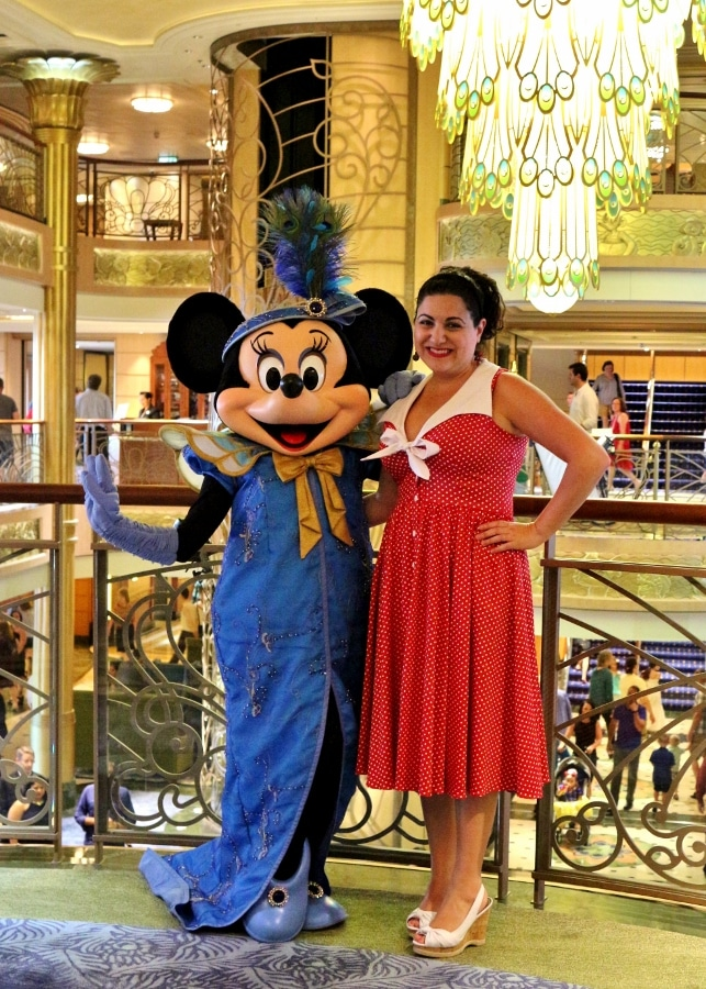 a woman posing with Minnie Mouse dressed in a formal gown