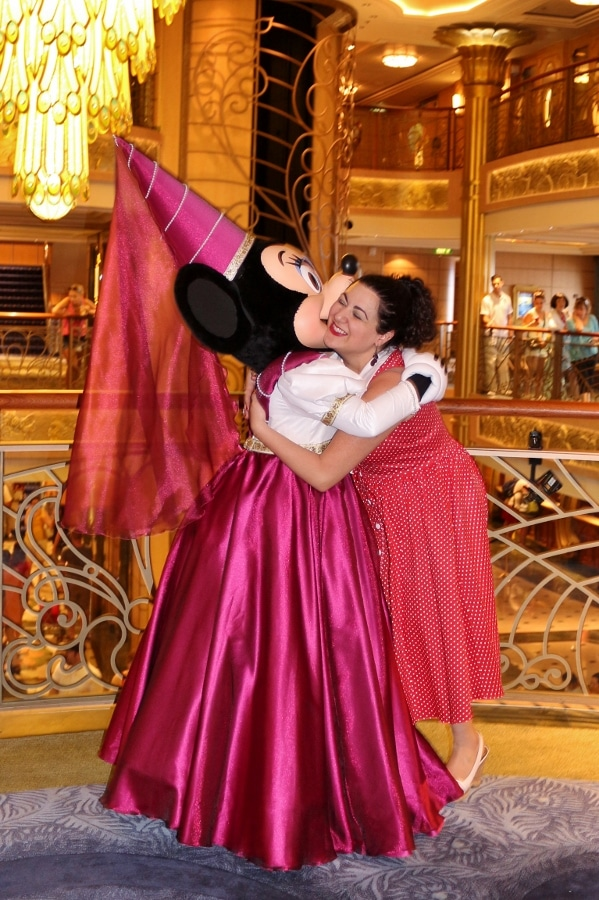 a woman hugging Minnie Mouse dressed as a princess