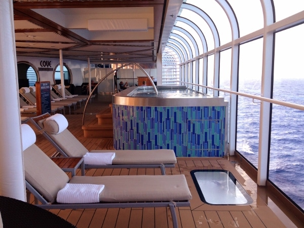 outdoor lounge chairs and a hot tub overlooking the ocean on a cruise ship
