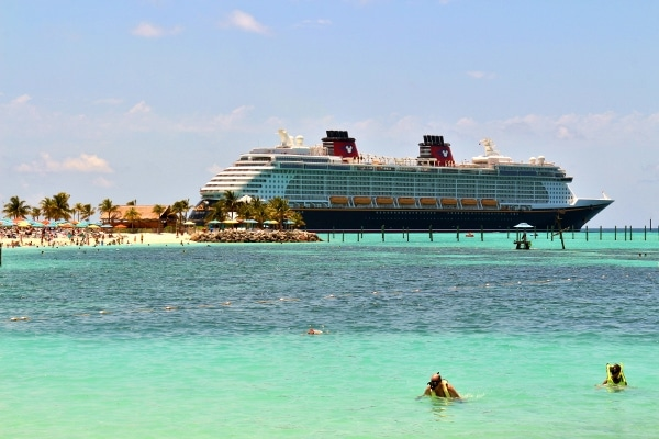 a group of snorkelers at a beach with the Disney Fantasy cruise ship in the background