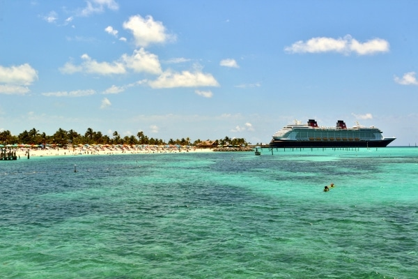 a wide view of a beach at Castaway Cay with the Disney Fantasy in the background