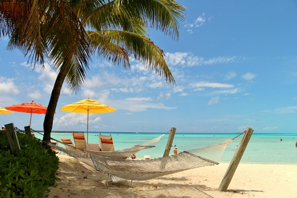 hammocks and beach chairs in the shade of a palm tree on a Caribbean beach