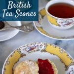 a dainty English scone topped with jam, and served on a chine plate with a cup of tea to the side