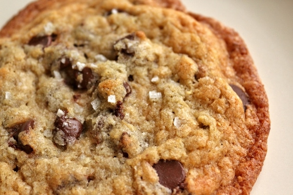 A close up of a large salted chocolate chip cookie. You can see the flakes of coarse sea salt on top