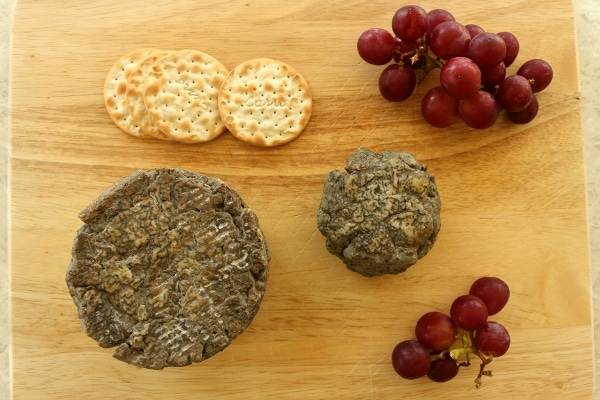 uncut wheels of blue cheese with crackers and red grapes on a wooden board