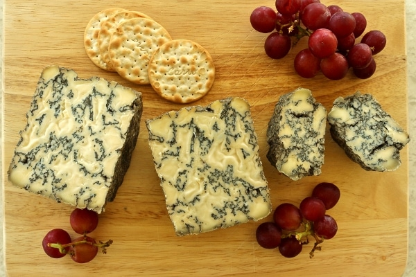 overhead view of homemade wheels of blue cheese cut in half on a wooden board