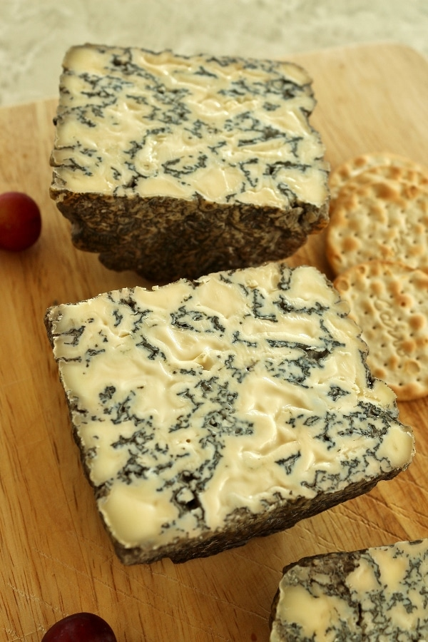 a small halved wheel of blue cheese with crackers on a wooden board