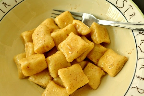 a bowl of gnocchi in a brown butter sauce