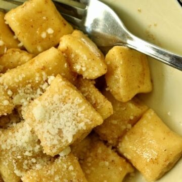 a closeup of a bowl of dunderi gnocchi in brown butter topped with grated cheese